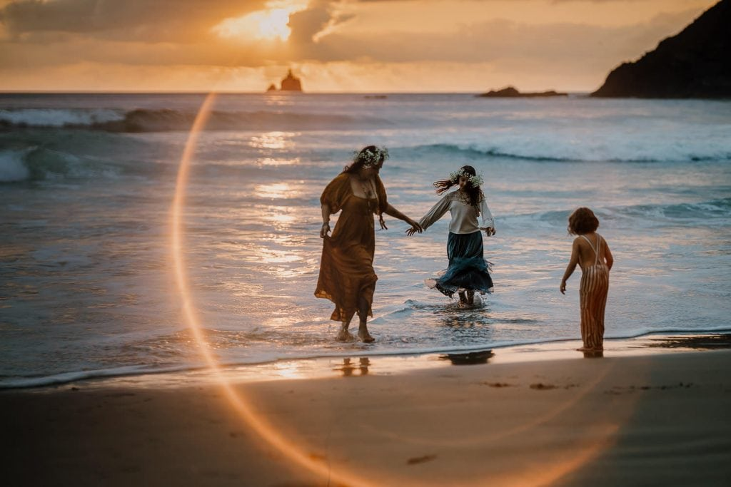 Family running from the waves with tillamook rock lighthouse behind them at sunset