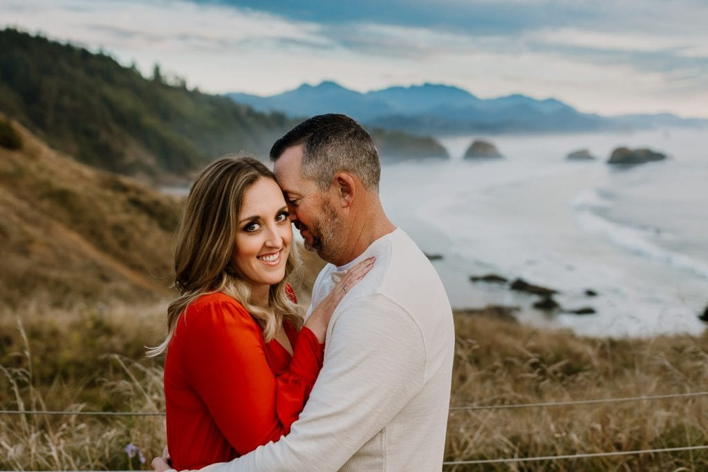 Couple holding each other with cloudy beach skies behind them
