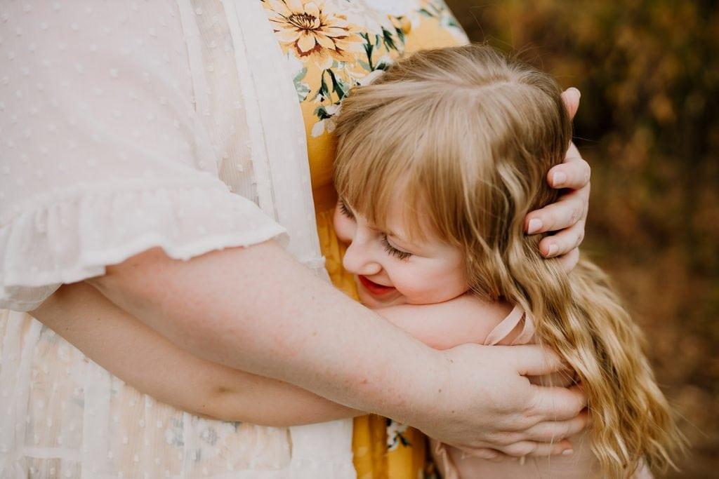 Little girl hugging her mom tight