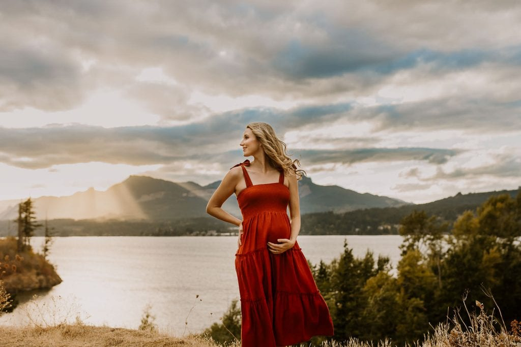 Beautiful pregnant woman standing with wind in hair on a cloudy day edited with Lightroom presets