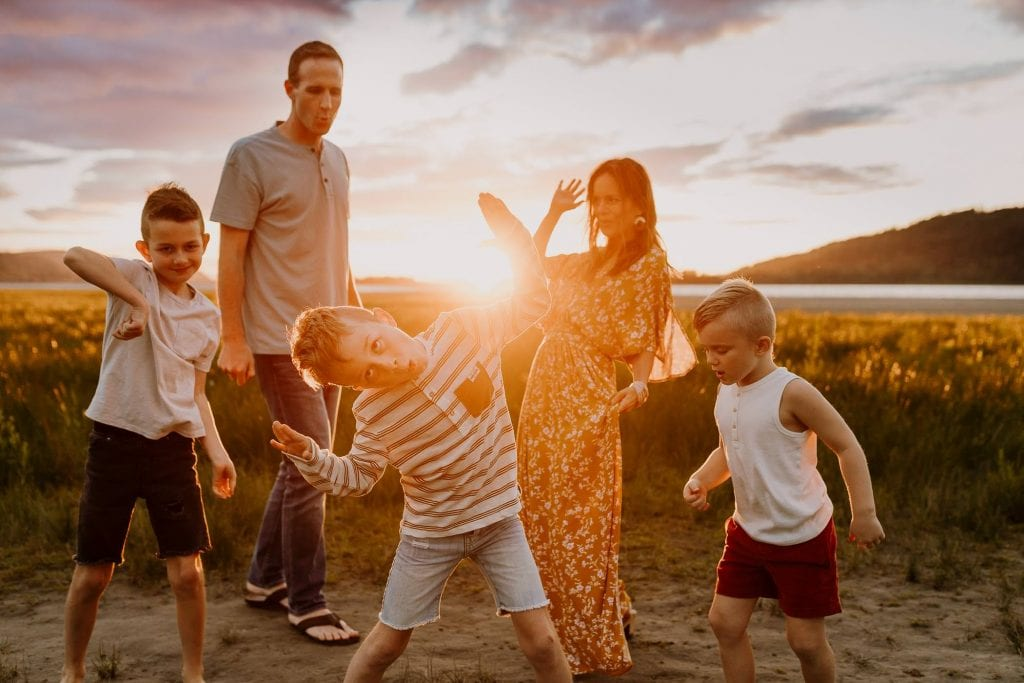 Family with boys dancing together at sunset and being silly in Oregon