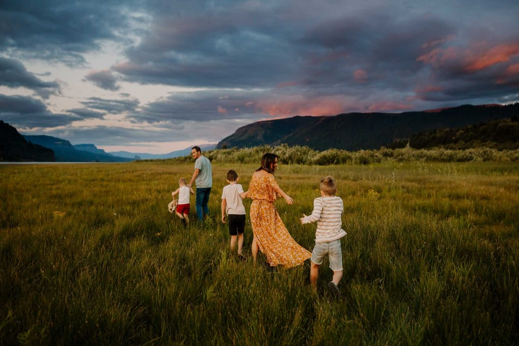 family in portland oregon running from the camera in field of grass